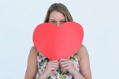 Mujer que sostiene la tarjeta del corazón Fotos de archivo
