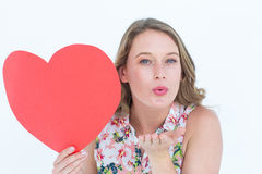 Mujer que sostiene la tarjeta del corazón y que sopla beso Foto de archivo