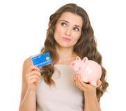Mujer que sostiene la tarjeta y la hucha de crédito fotografía de archivo libre de regalías