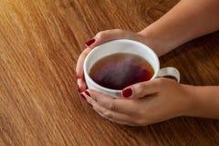 Mujer que sostiene la taza caliente de té imagen de archivo