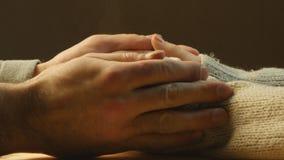Mujer que sostiene la taza de café, calentándose las manos Los brazos de los hombres alrededor de las manos de la mujer almacen de video