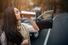 Mujer que sostiene la taza de café disponible al lado del coche Ciérrese encima de la mano Concepto del otoño Viaje del bosque de fotografía de archivo