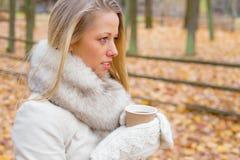 Mujer que sostiene la taza de café y que mira a AR la visión Fotografía de archivo