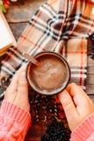 Mujer que sostiene la taza de chocolate caliente Chocolate caliente en tabl de madera Imágenes de archivo libres de regalías
