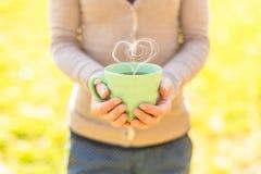 Mujer que sostiene la taza de té caliente con forma del corazón Imagenes de archivo