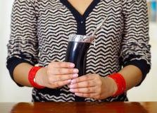 Mujer que sostiene la taza tradicional del compañero con la paja típica del metal que se pega para arriba, bebida herbaria surame Fotos de archivo libres de regalías