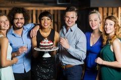 Mujer que sostiene la torta de cumpleaños con sus amigos Foto de archivo libre de regalías