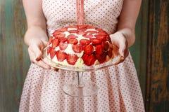 Mujer que sostiene la torta de la fresa en soporte de la torta Fotos de archivo