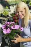 Mujer que sostiene las flores en retrato del cuarto de niños de la planta Imagen de archivo