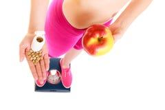 Mujer que sostiene las vitaminas y la manzana Cuidado médico Imagen de archivo