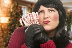 Mujer que sostiene los bastones de caramelo en el ajuste de la Navidad Fotos de archivo libres de regalías
