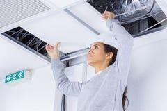 Mujer que sostiene los cables de arriba en roofspace imagen de archivo