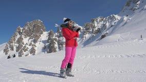 Mujer que sostiene los esquís en sus hombros, esquiadores del fondo que esquían en centro turístico de montaña almacen de video