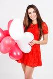 Mujer que sostiene los globos rojos del corazón Fotos de archivo