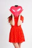 Mujer que sostiene los globos rojos del corazón Imagenes de archivo
