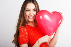 Mujer que sostiene los globos rojos del corazón Fotos de archivo libres de regalías