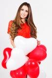 Mujer que sostiene los globos rojos del corazón Imagen de archivo libre de regalías