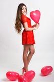 Mujer que sostiene los globos rojos del corazón Fotografía de archivo libre de regalías