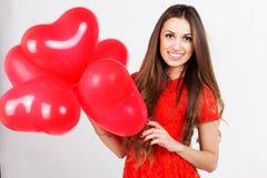 Mujer que sostiene los globos rojos del corazón Foto de archivo