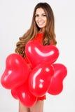 Mujer que sostiene los globos rojos del corazón Imágenes de archivo libres de regalías