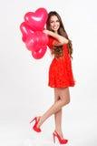 Mujer que sostiene los globos rojos del corazón Imagen de archivo