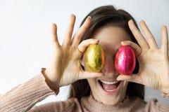 Mujer que sostiene los huevos de Pascua azules y rojos del chocolate delante de sus ojos fotografía de archivo libre de regalías