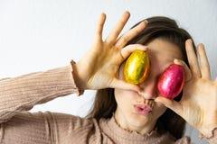 Mujer que sostiene los huevos de Pascua rojos y de oro del chocolate delante de sus ojos fotos de archivo libres de regalías