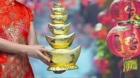 Mujer que sostiene los lingotes chinos del oro del Año Nuevo en Chinatown metrajes