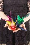 Mujer que sostiene los pájaros de papel de diversos colores Foto de archivo libre de regalías