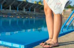 Mujer que sostiene los pantalones de los vaqueros por la piscina Fotos de archivo libres de regalías