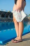 Mujer que sostiene los pantalones de los vaqueros por la piscina Foto de archivo libre de regalías