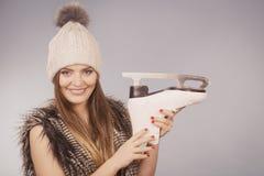 Mujer que sostiene los patines de hielo, deporte de invierno Foto de archivo libre de regalías