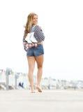 Mujer que sostiene los pcteres de ruedas que caminan descalzo Imagen de archivo