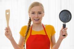 Mujer que sostiene los utensilios de cocinar Imagen de archivo