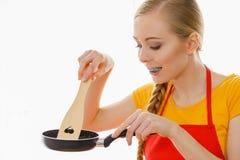 Mujer que sostiene los utensilios de cocinar Fotos de archivo libres de regalías