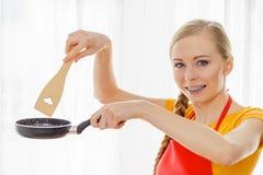Mujer que sostiene los utensilios de cocinar Imagenes de archivo