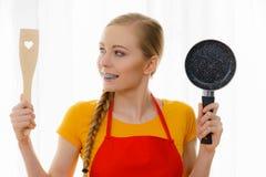 Mujer que sostiene los utensilios de cocinar Imagen de archivo libre de regalías