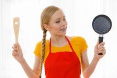 Mujer que sostiene los utensilios de cocinar Fotografía de archivo libre de regalías