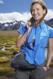 Mujer que sostiene los zapatos por la charca de la montaña Imagen de archivo