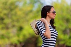 Mujer que sostiene los zapatos sobre su imagen de la acción del hombro Foto de archivo libre de regalías