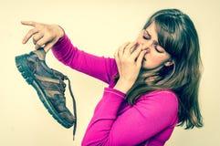 Mujer que sostiene los zapatos stinky sucios - estilo retro Fotos de archivo