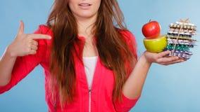 Mujer que sostiene píldoras y las frutas Cuidado médico Foto de archivo libre de regalías