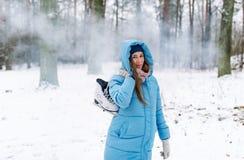 Mujer que sostiene patines de hielo al aire libre en nieve Fotos de archivo libres de regalías