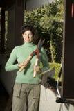 Mujer que sostiene podadoras del seto - vertical Imagen de archivo