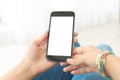 Mujer que sostiene smartphone con la pantalla en blanco fotos de archivo
