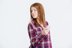 Mujer que sostiene smartphone y que mira lejos Fotos de archivo