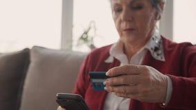 Mujer que sostiene su tarjeta plástica y celular maduros en manos almacen de metraje de vídeo