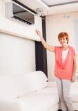 Mujer que sostiene un acondicionador de aire teledirigido foto de archivo libre de regalías