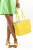 Mujer que sostiene un bolso de compras amarillo Imagen de archivo libre de regalías