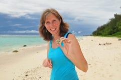 Mujer que sostiene un cangrejo en una playa Foto de archivo